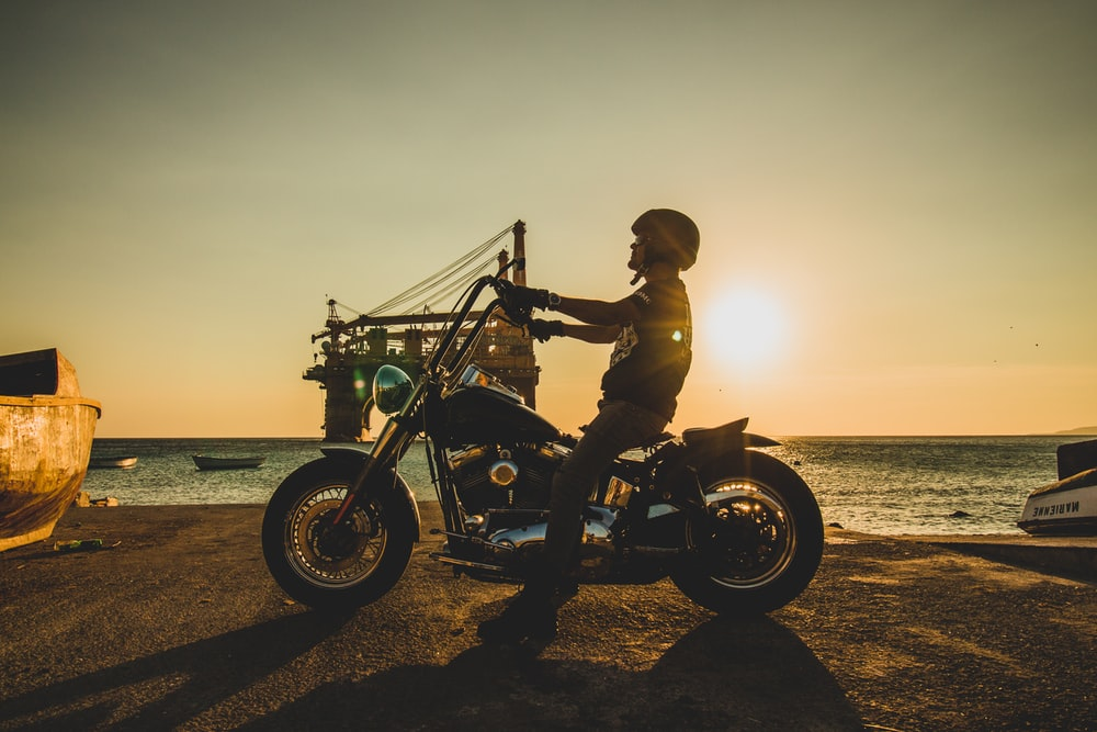man riding motorcycle on beach during sunset