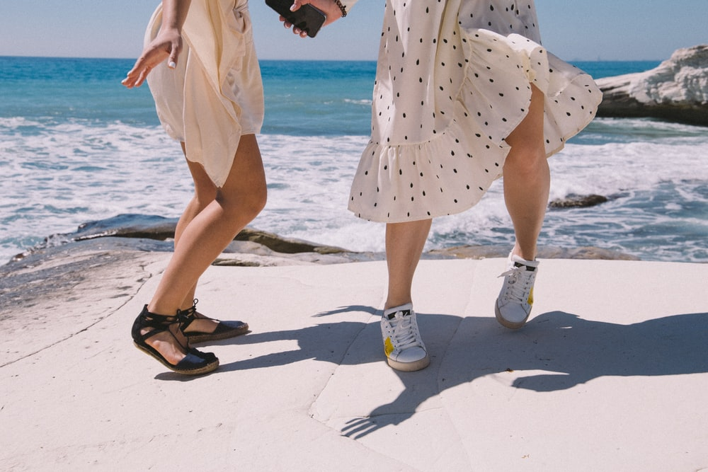 woman in yellow and white polka dots dress and white shoes standing on beach during daytime