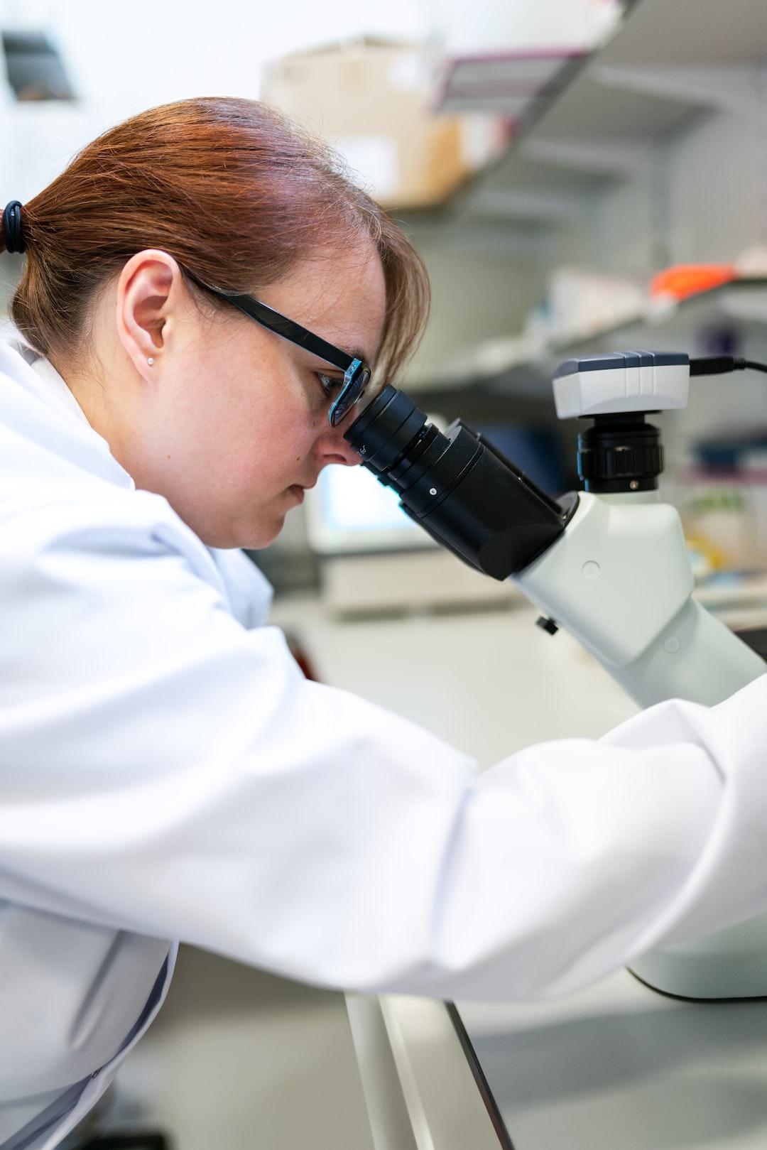 Female biomedical engineer uses microscope