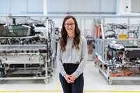 Woman in glasses on a factory floor smiling