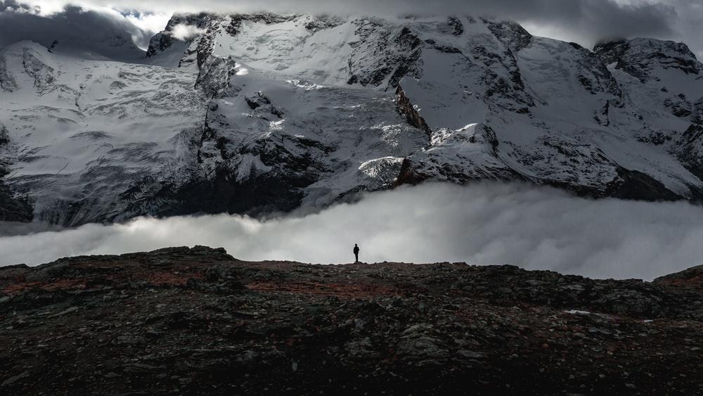 person standing on rock mountain