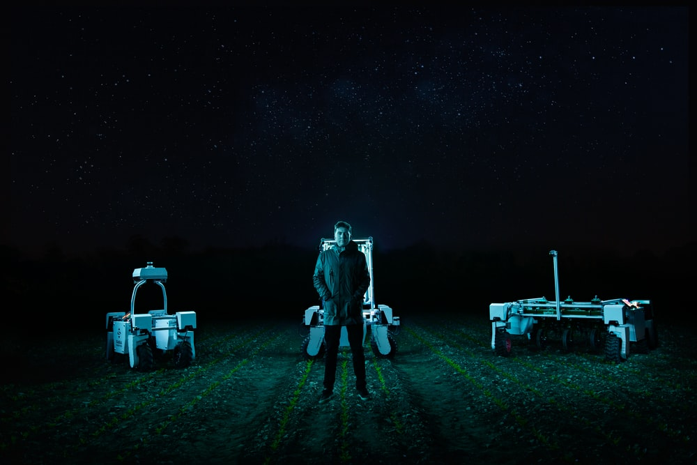 man and woman standing beside each other on green grass field during night time