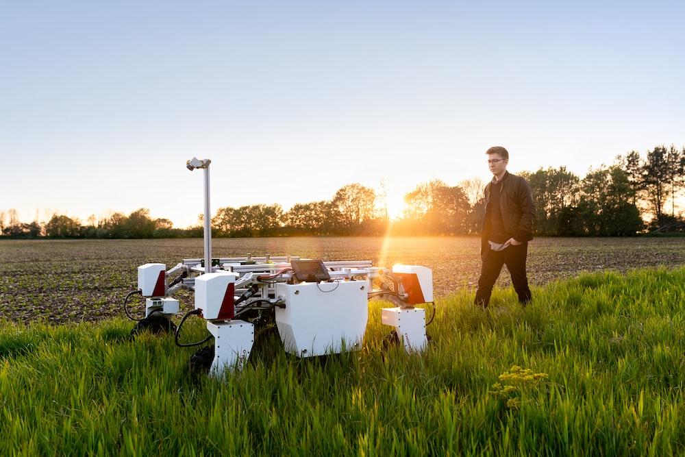 man in brown shirt standing on green grass field during sunset