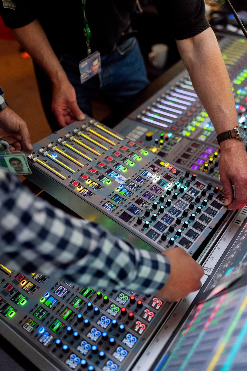 person in green and white checkered long sleeve shirt playing audio mixer