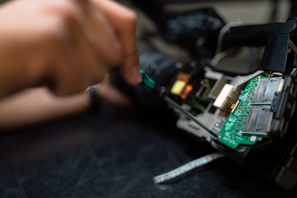 person holding green and black circuit board