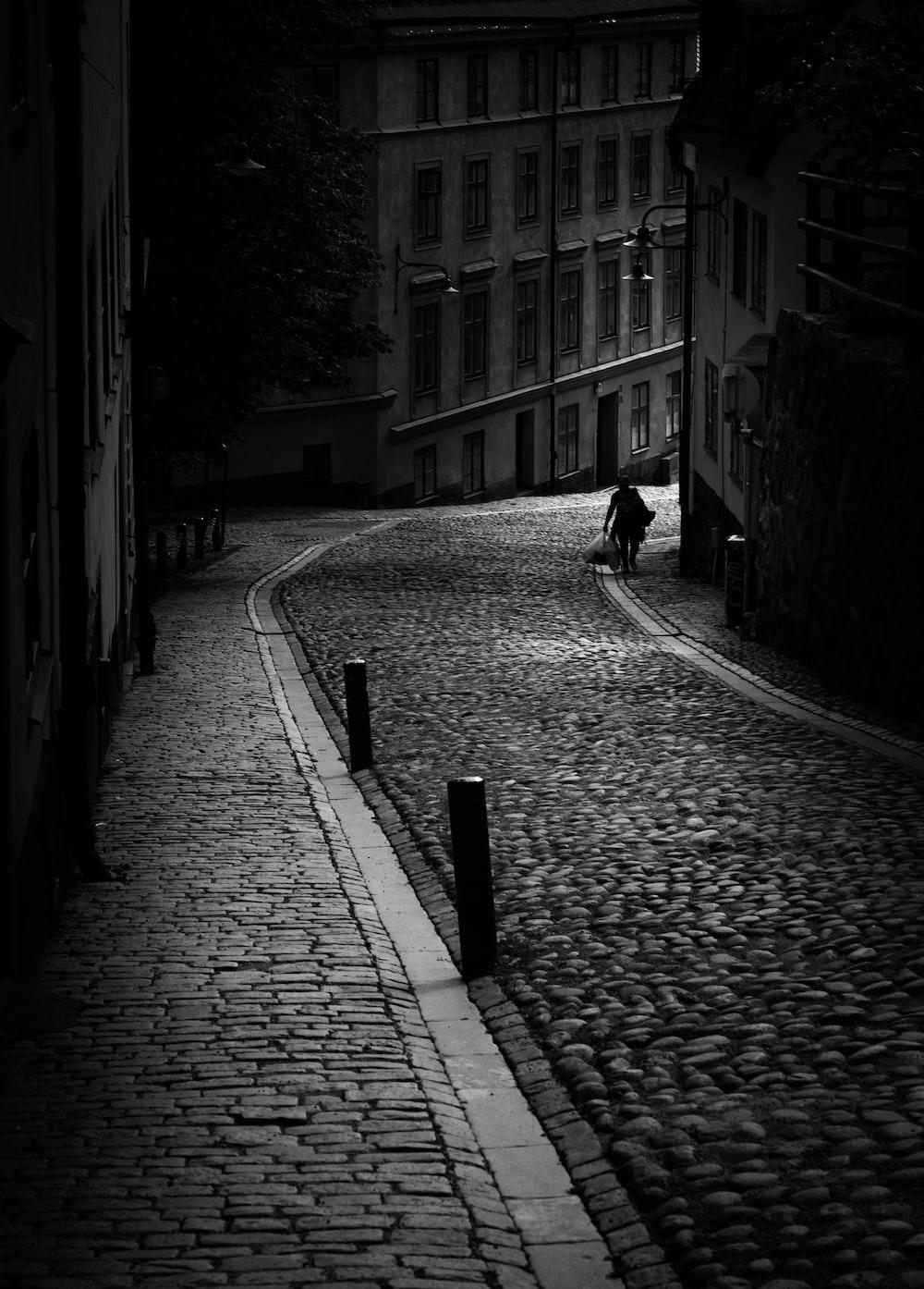 grayscale photo of person walking on sidewalk