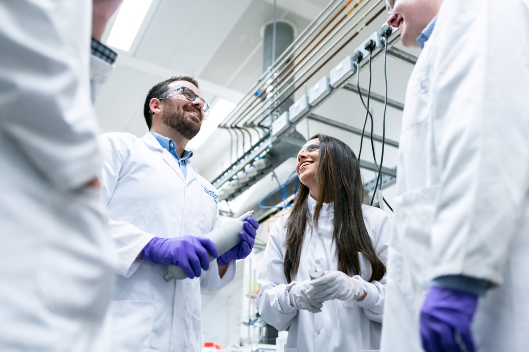 Chemical engineers talk in laboratory