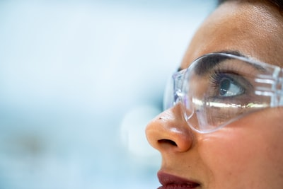 woman wearing silver framed eyeglasses science teams background