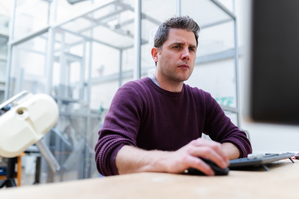 man in purple sweater sitting at the table