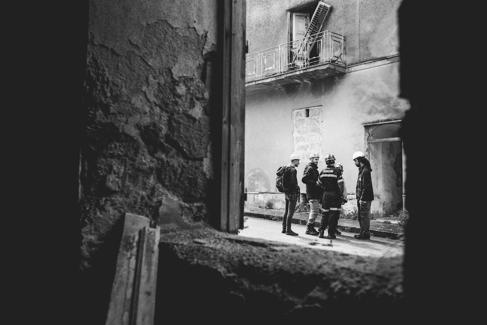grayscale photo of 2 men walking on street