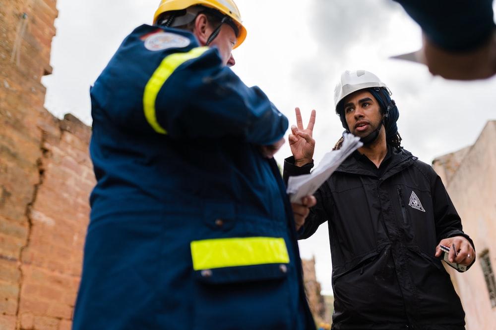 dois homens de capacetes conversando de pé, em meio a uma obra
