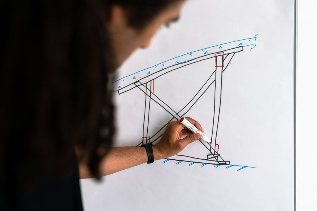 Male structural engineer draws on whiteboard
