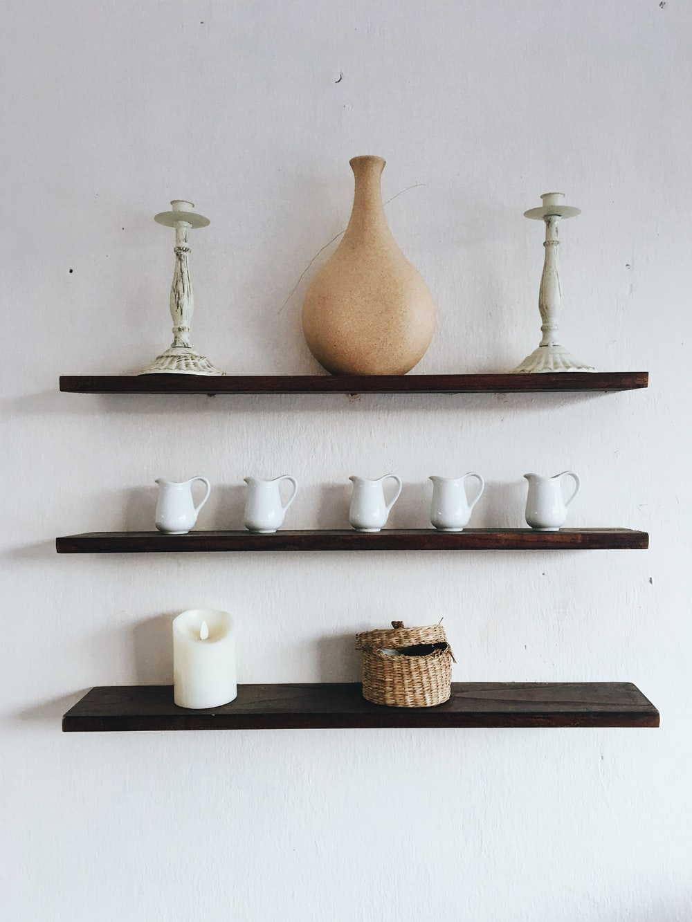 white and brown ceramic vase on white wooden shelf