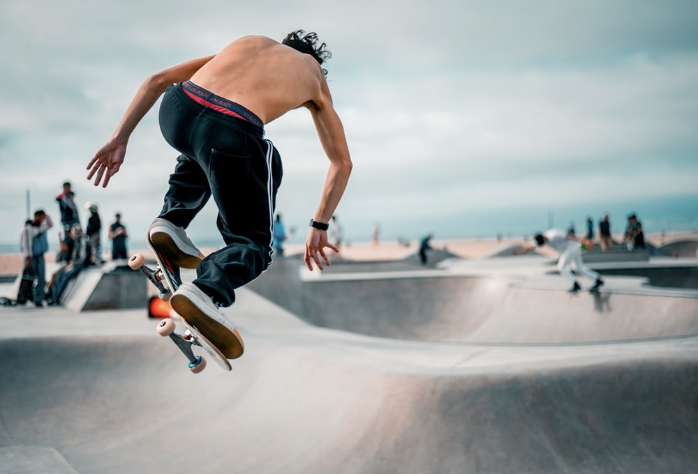 man in black tank top and blue denim jeans doing skateboard stunts