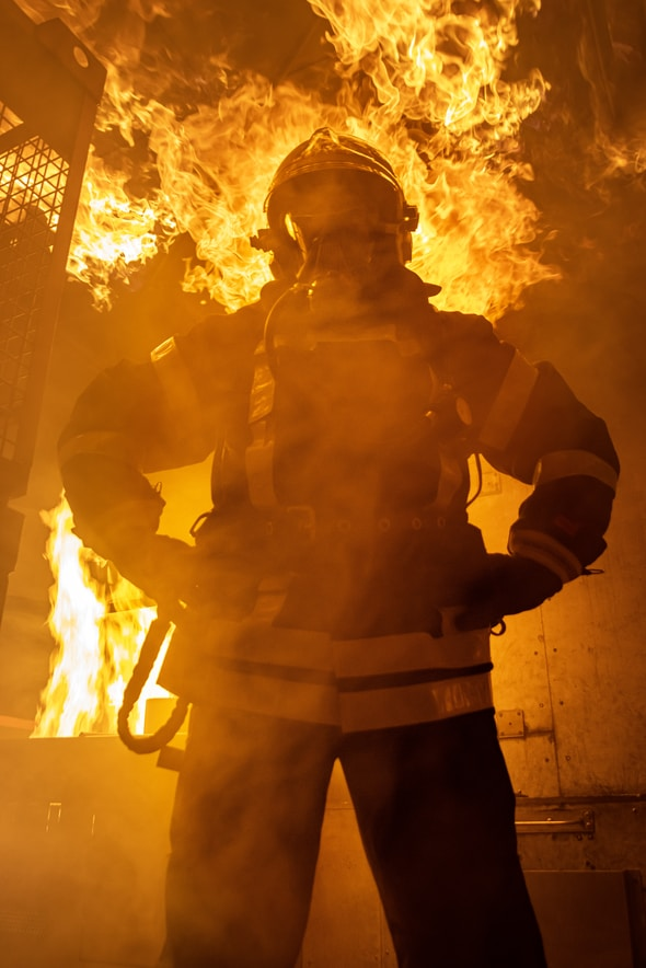 man in black and yellow jacket standing near fire