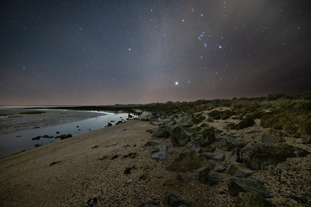 brown rocky shore under blue sky during night time