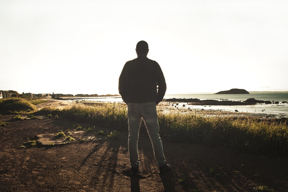 man in black jacket standing on brown field during daytime
