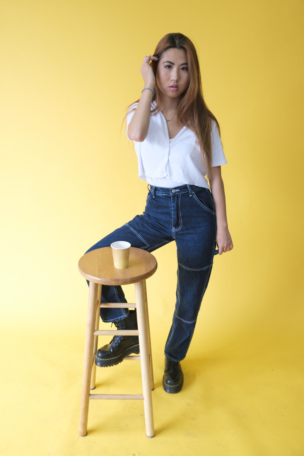 woman in white shirt and blue denim jeans standing beside brown wooden stool