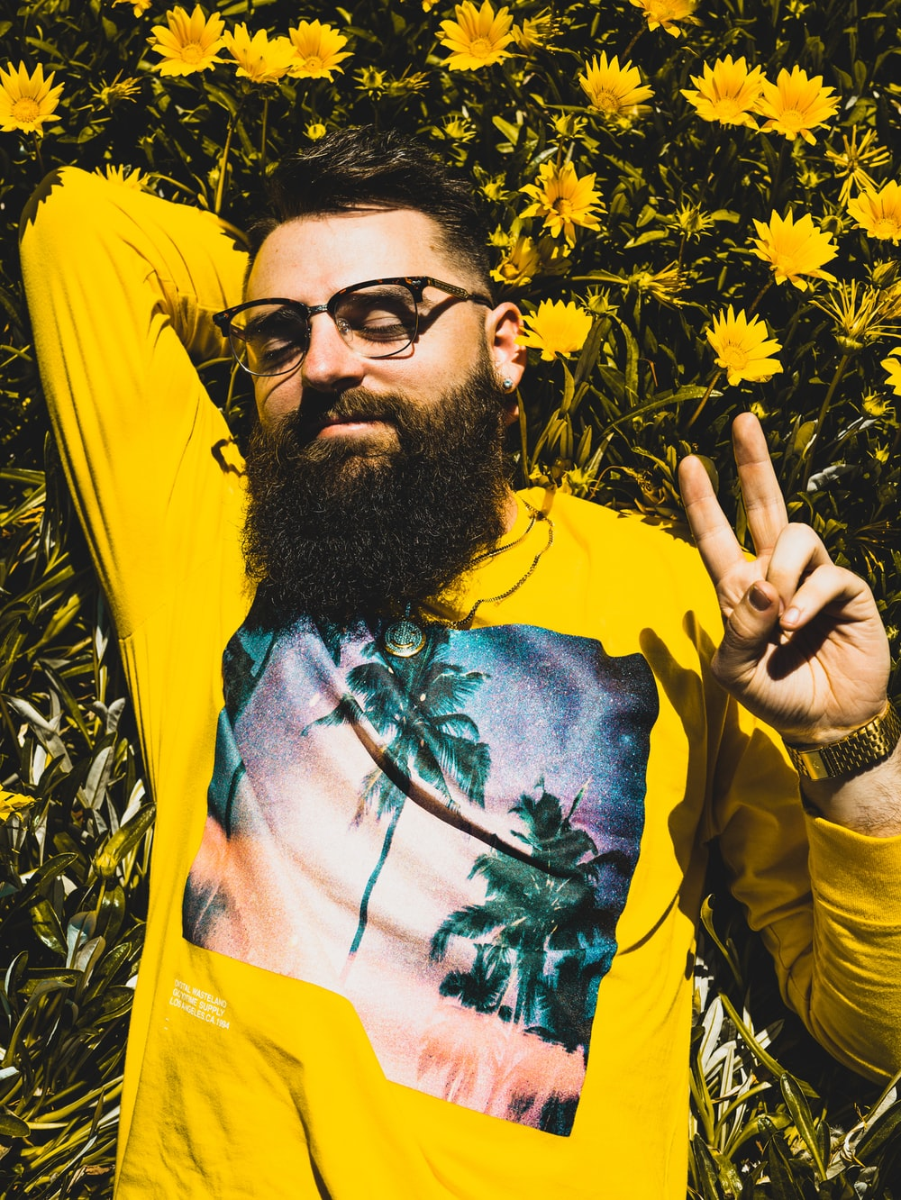 man in green yellow and red floral shirt wearing black sunglasses