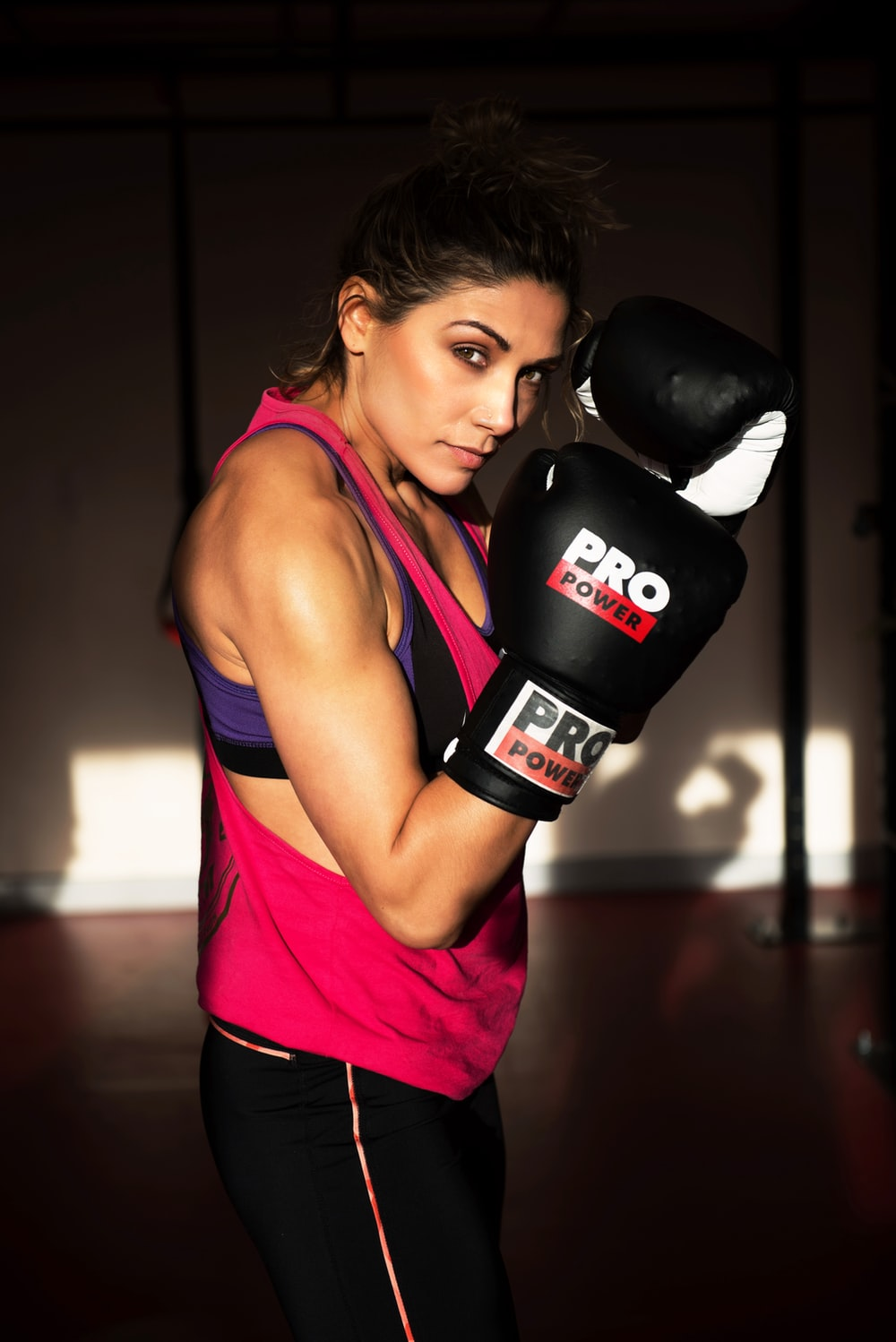 woman in pink tank top and black boxing gloves