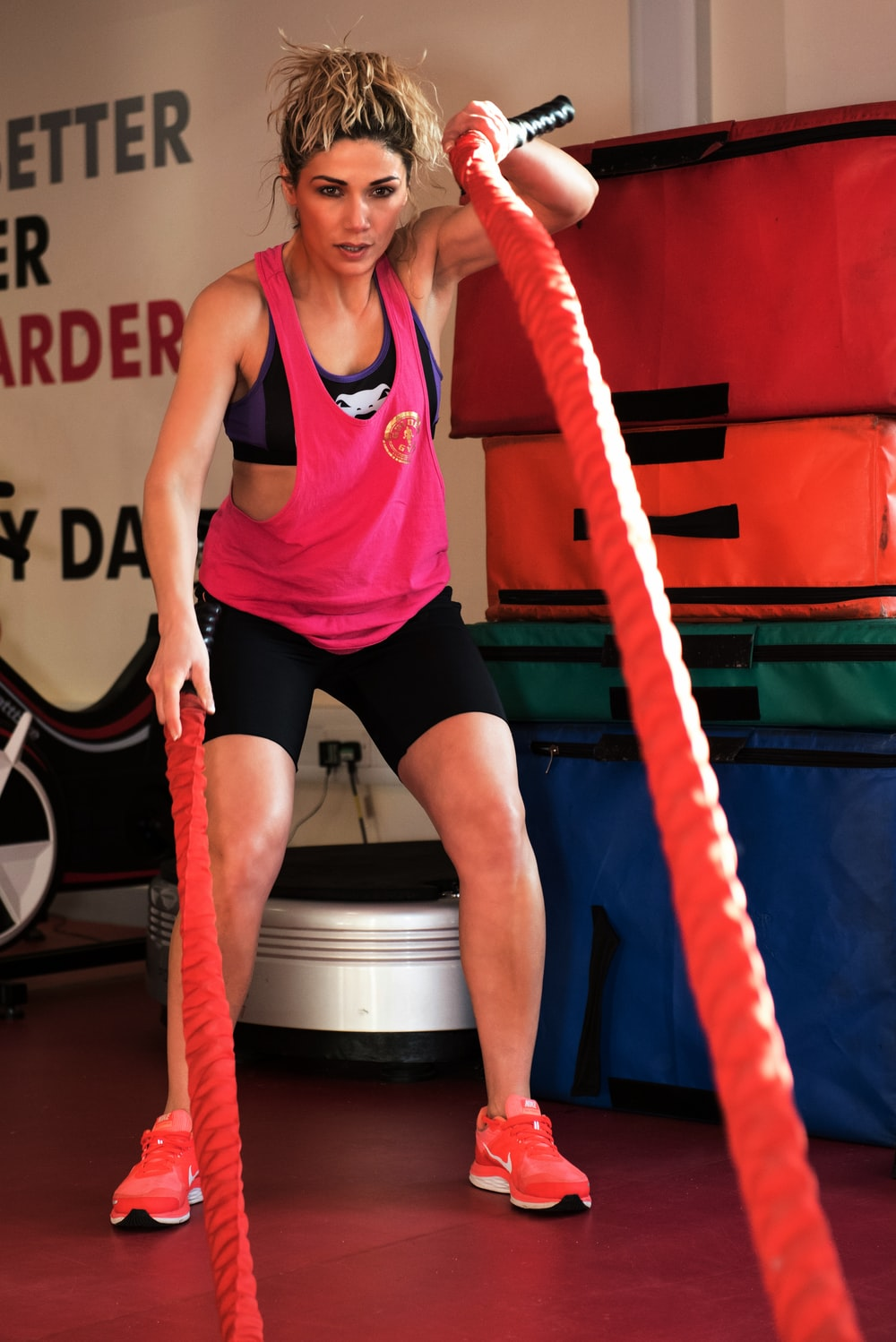 woman in red and black tank top and black shorts sitting on black and white exercise