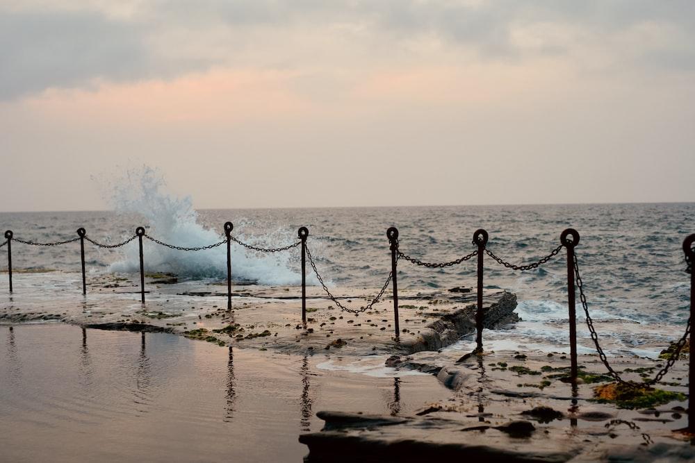 black metal fence on seashore during daytime