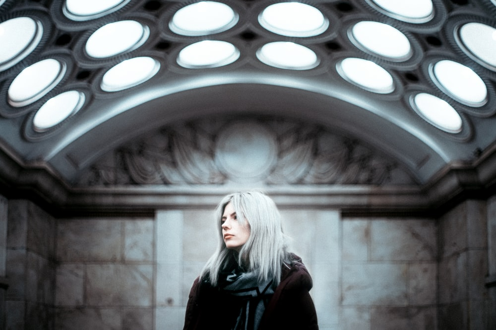 woman in black jacket standing in front of round window