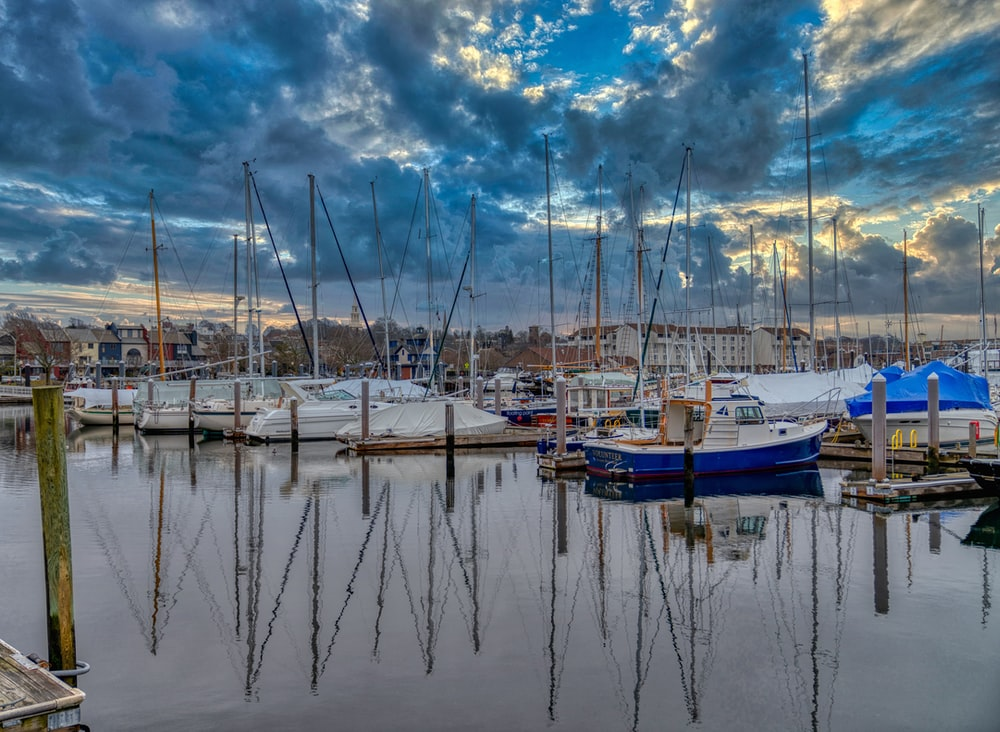 white and blue boats on body of water under blue and white cloudy sky during daytime