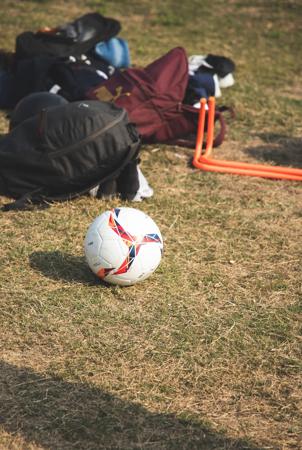 white and red soccer ball on green grass field