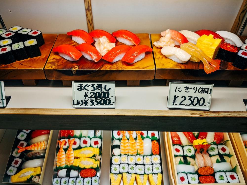assorted sushi on white wooden shelf