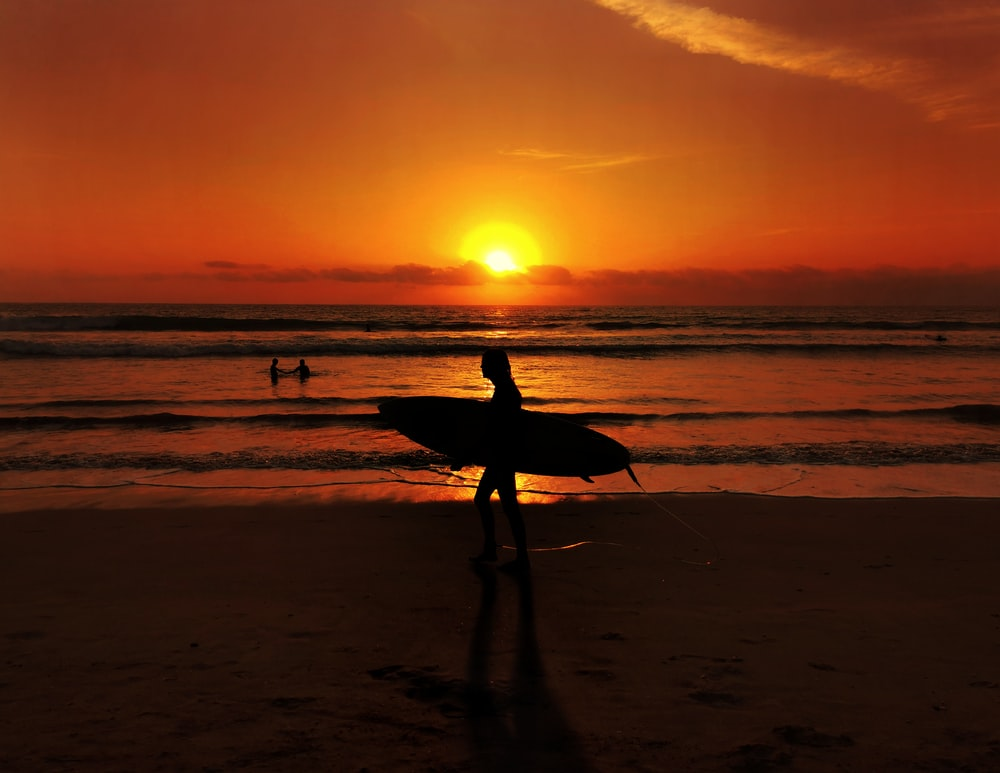 silhouette of man holding surfboard walking on beach during sunset