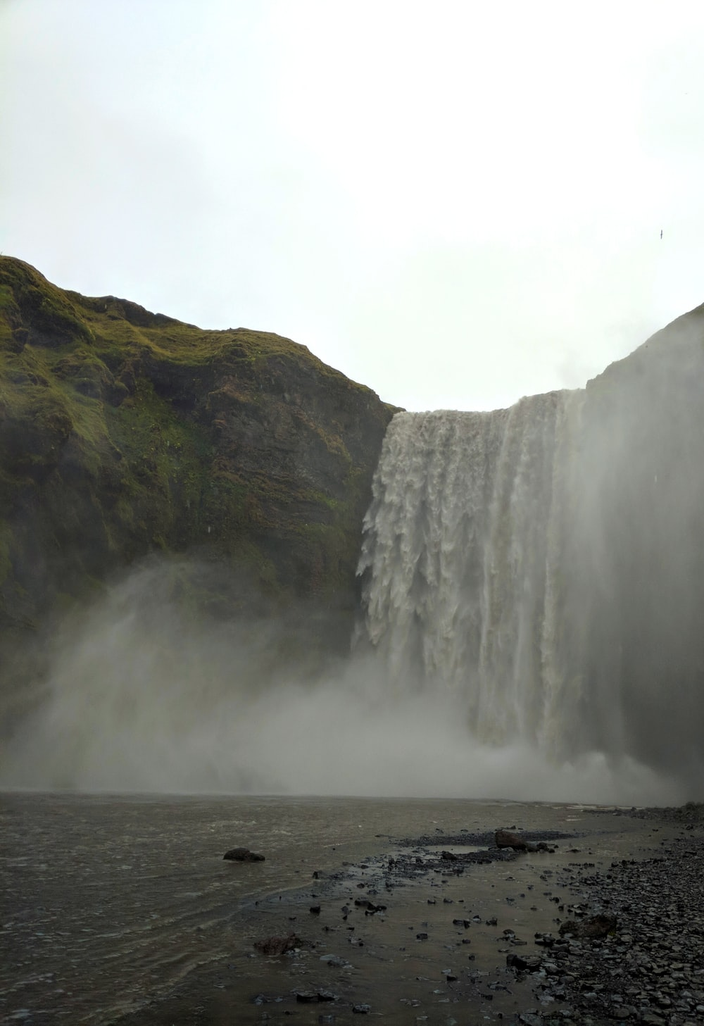 waterfalls on gray rocky mountain during daytime
