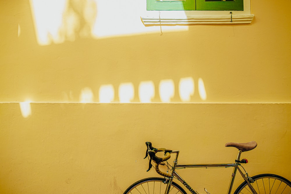black bicycle parked beside white wall