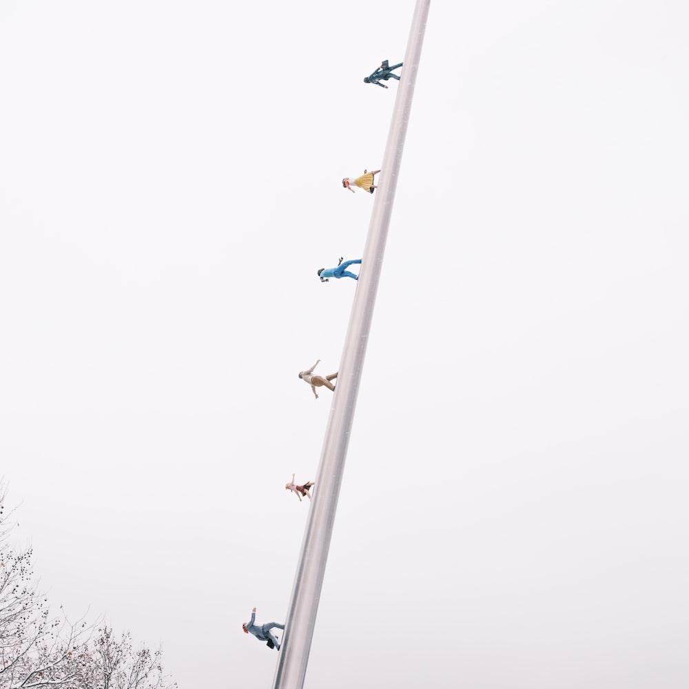 flock of birds on electric post under gray sky