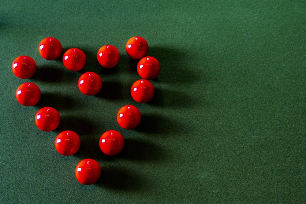 red round beads on green textile