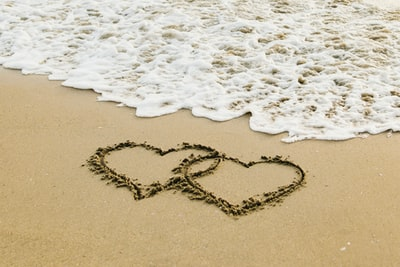 white sand with heart shaped sand hearts teams background