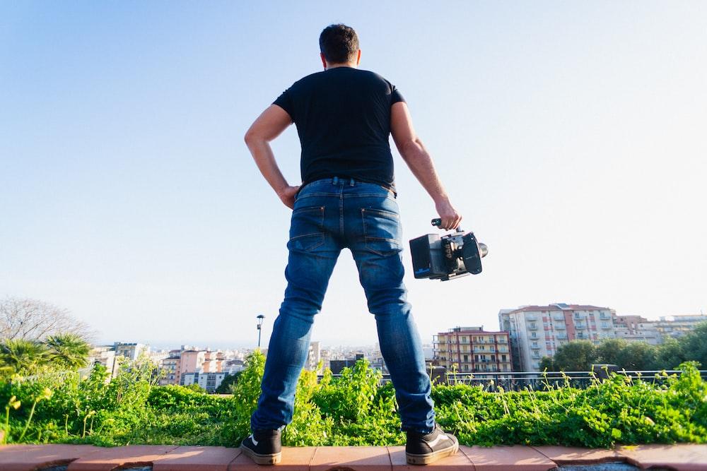 man in black t-shirt and blue denim jeans holding black camera