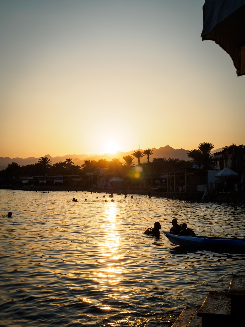 silhouette of people riding boat on body of water during sunset