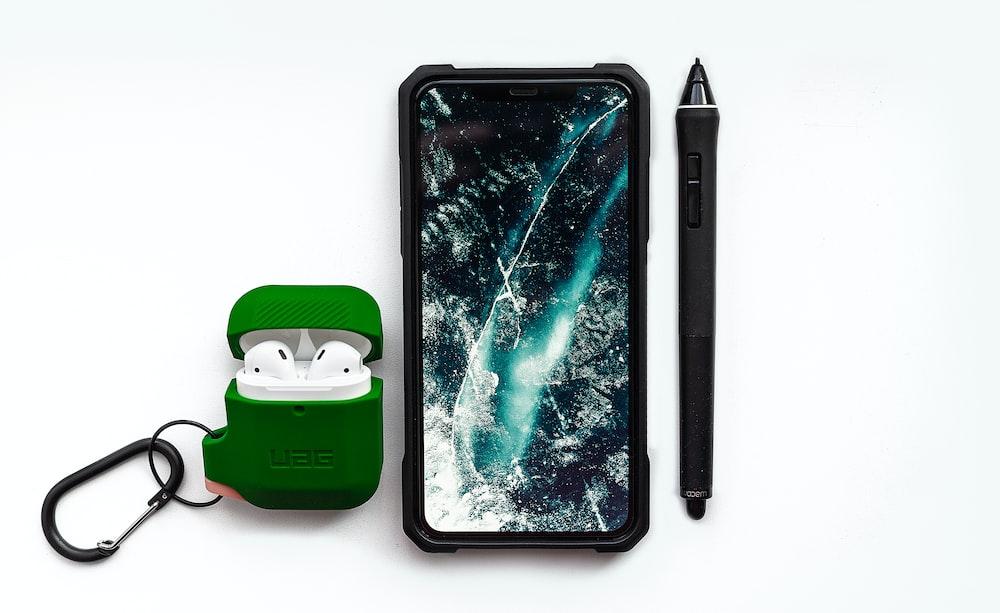 black smartphone beside black pen
