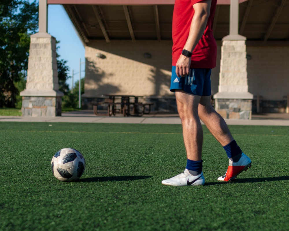 man in red shirt and blue shorts playing soccer during daytime