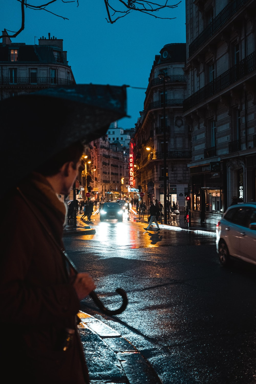 person in brown coat holding umbrella walking on sidewalk during night time