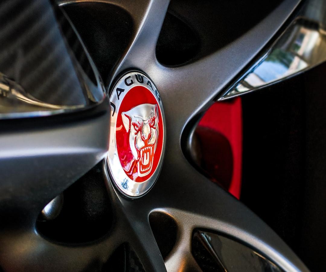 Carbon Fiber Jaguar Wheel featuring red emblem and brake caliper.