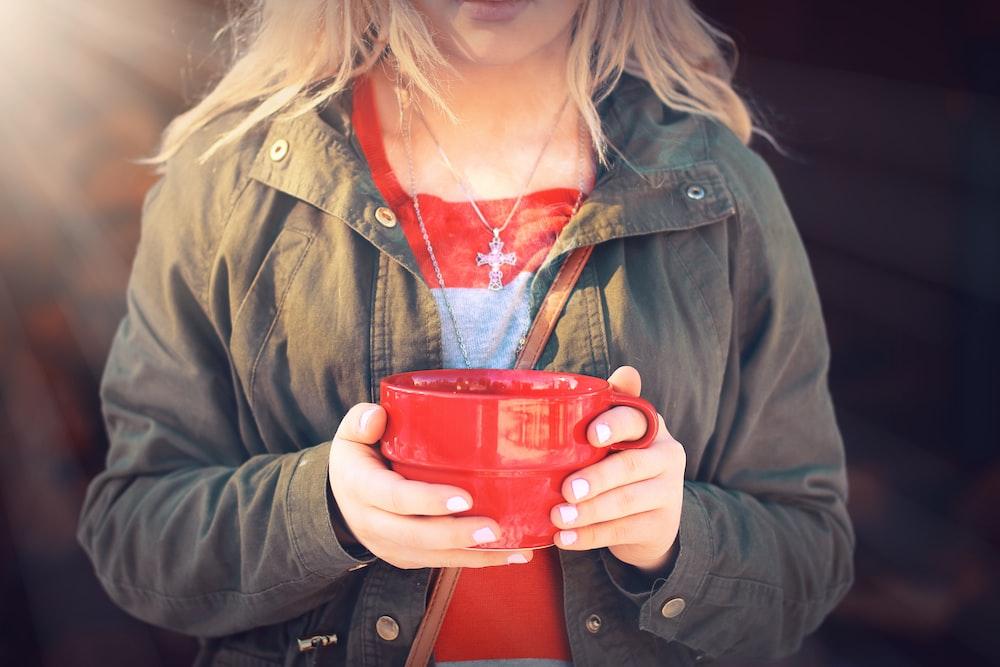 woman in green jacket holding red ceramic mug