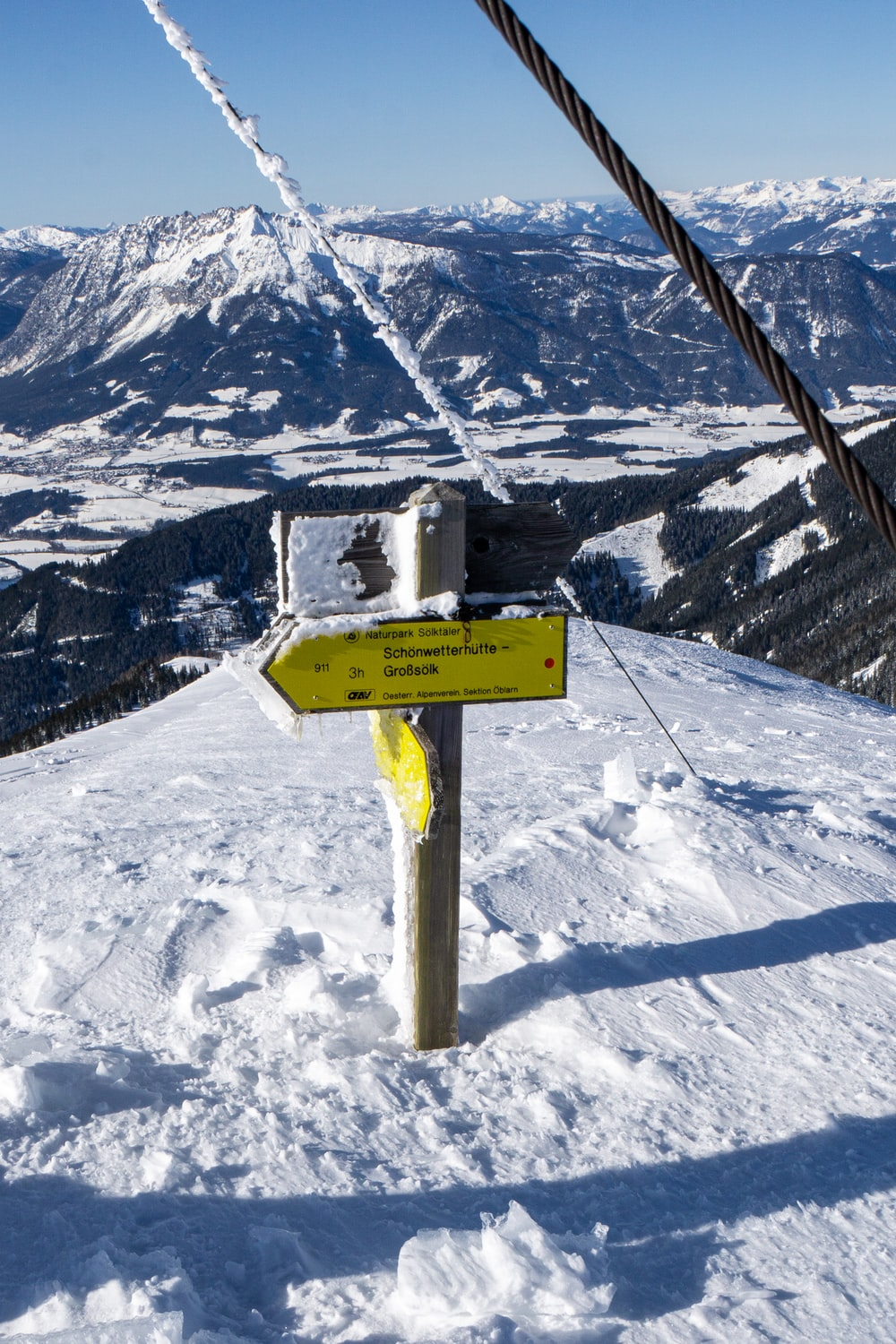 white and yellow signage on brown wooden post on snow covered mountain during daytime