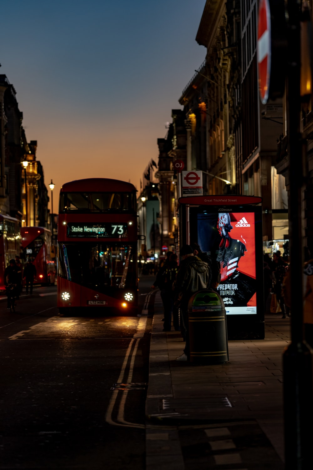 red and black tram on the street during night time