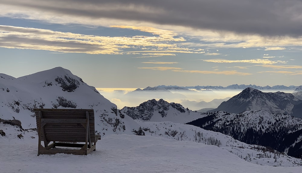 brown wooden bench on snow covered mountain during daytime
