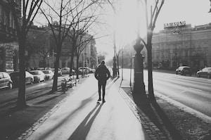 person in black coat walking on sidewalk during daytime