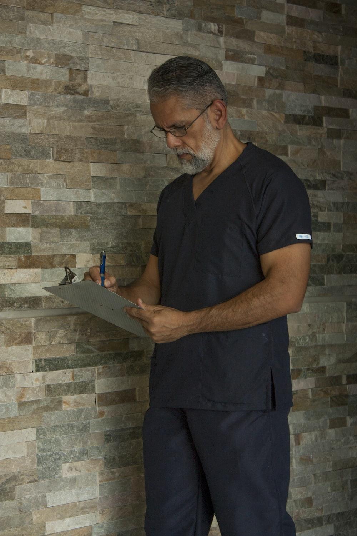 man in black crew neck t-shirt holding black tablet computer