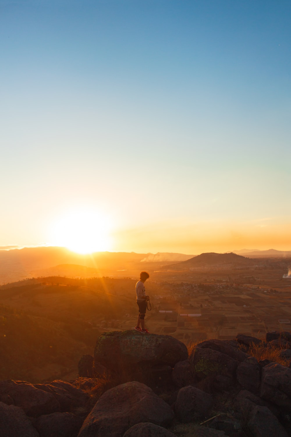man standing on rock formation during sunset