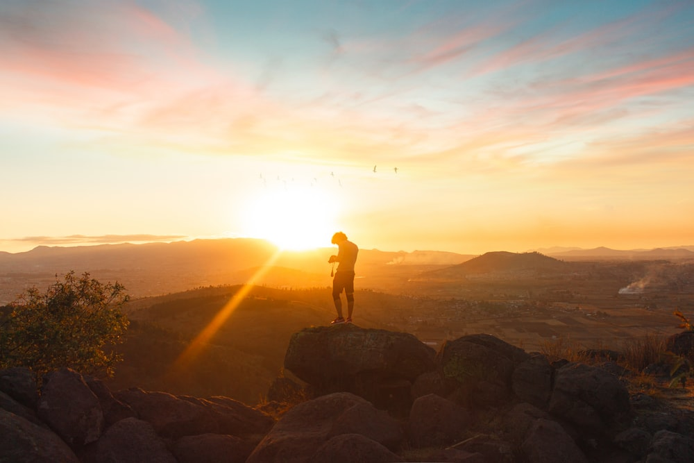 silhouette of man standing on rock during sunset